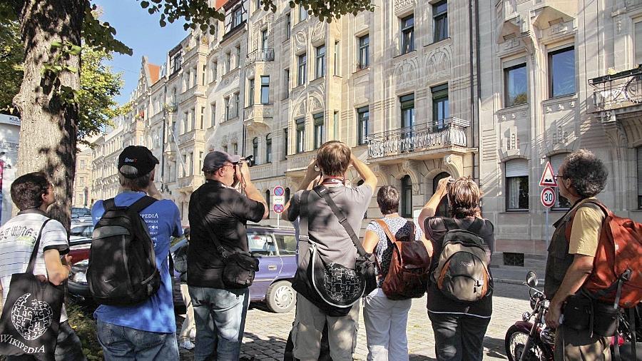 """Im Rahmen des Fotowettbewerbs """"Wiki Loves Monuments"""" fingen die von Stadtheimatpfleger Alexander Mayer (re.) geführten Besucher auch Motive der Fürther Prachtstraße Hornschuchpromenade ein."""