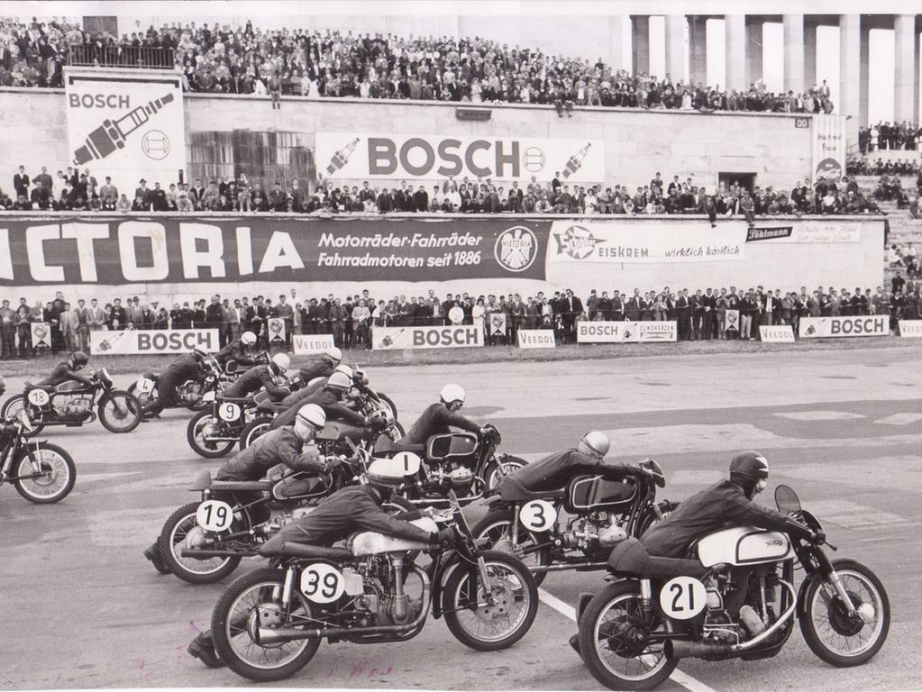 Foto: Norisring-Rennen, Datum unbekannt, vermutl. 50er oder 60er Jahre Motiv: Motorradrennen, die Fahrer schieben ihre Maschinen an den Start; im Hintergrund Zeppelintribüne, Aufnahmedatum: unbekannt