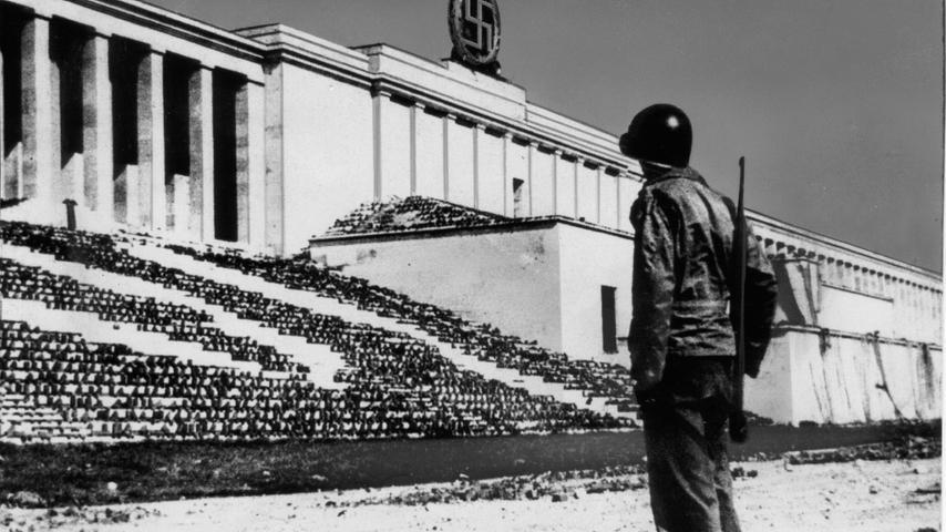 1945 ist die Niederlage des NS-Regimes besiegelt: Ein amerikanischer Soldat hält am 20. April  Wache vor der Zeppelintribüne. Ihre Stufen sind mit Tarnnetzen bespannt. Das vergoldete Hakenkreuz im Lorbeerkranz wird etwas später bei einer Siegesparade gesprengt und ...