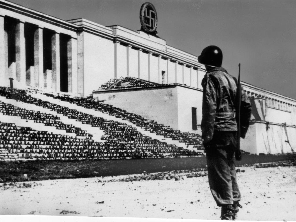 Die Niederlage des NS-Regimes ist besiegelt: Ein amerikanischer Soldat hält am 20. April 1945 Wache vor der Zeppelintribüne. Ihre Stufen sind mit Tarnnetzen bespannt. Das vergoldete Hakenkreuz im Lorbeerkranz wird bei einer Siegesparade gesprengt.