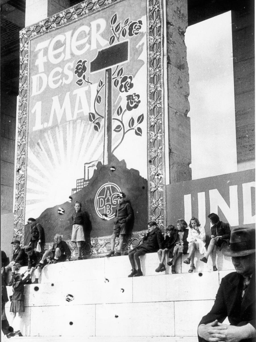 unter einem Maiplakat, das einen blühenden Hammer als Zeichen friedlicher Arbeit und eine aufgehende Sonne als Symbol des neuen Anfangs zeigt. Die NN schrieben: