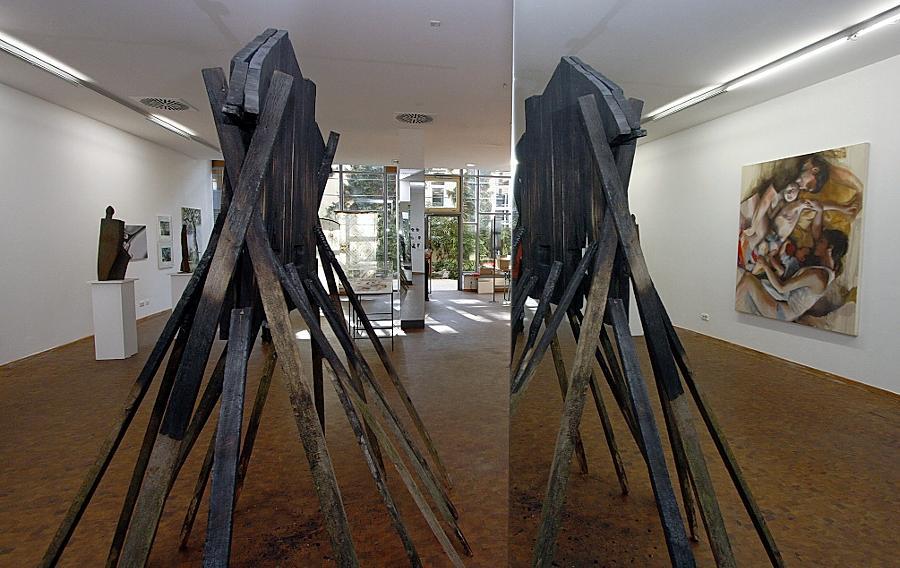 Blick in die Ausstellung des BBK: Im Vordergrund ist ein Werk von Walter Hettich zu sehen, das sich im Spiegel reflektiert. Das verbrannte Stück Holz thematisiert den Verlust von Heimat. Rechts ein Bild von Kathrin Hausel.