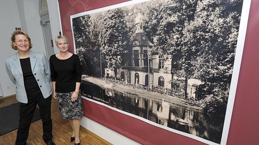Die Ausstellungsgestalterinnen Ruth Kollinger (li.) und Alexandra Herzog vor einem Banner mit einer historischen Fotografie des 1938 abgerissenen Stadtparkrestaurants am Schwanenweiher.