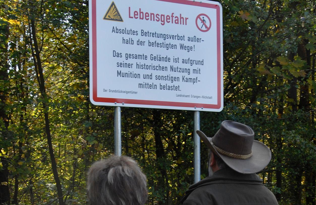 Diese Spaziergänger halten sich an die Warnschilder im Tennenloher Forst. Aber nicht jeder ist sich des Risikos bewusst, das im Boden liegt.