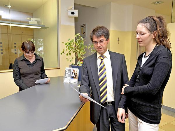 Vorstand Walter Frank im Gespräch mit Mitarbeiterin Nicole Sabransky. Hinter dem Thresen in der Eingangshalle steht Christina Neumeyer.