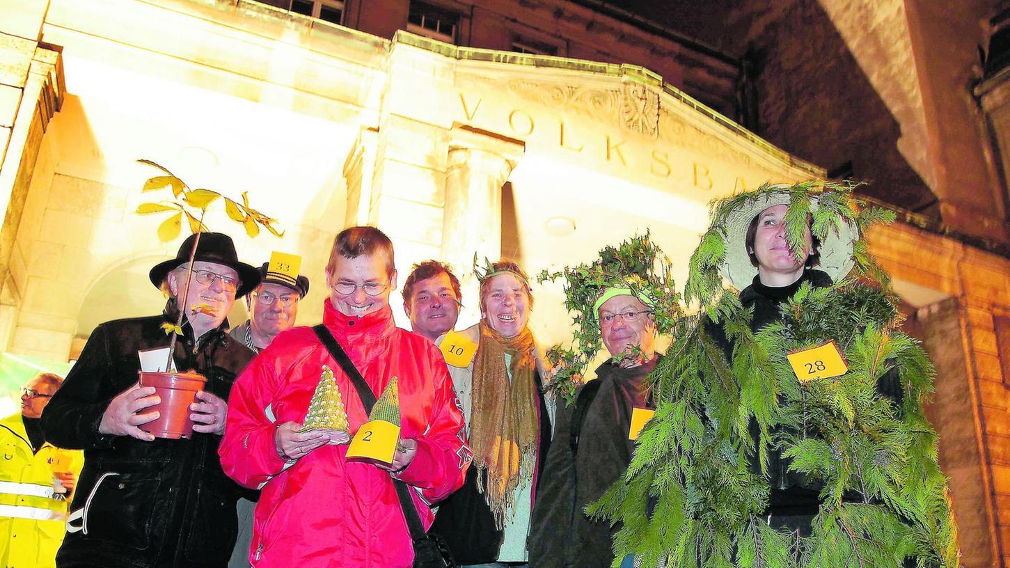 """Friedrich Popp (links) brachte einen kleinen Kastanienbaum im Topf mit, Monika König (Dritte von rechts) aus Schwabach führte eine """"Maulbeerbaum""""-Performance auf und Cornelia Hammerer erschien vor dem Volksbad als lebende Thujahecke (re.)."""