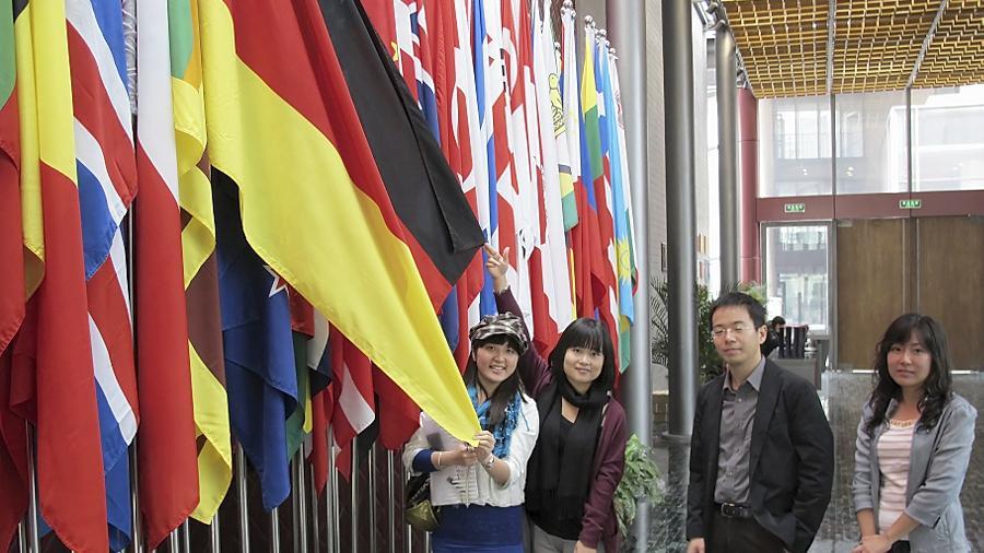 Im Konfuzius-Hauptquartier in Peking ist die deutsche Flagge nur eine unter 103 weiteren, repräsentiert aber immerhin elf Institute in Deutschland. Das freut Vize-Direktor Ding Cao (hier mit Mitarbeiterinnen des Instituts).