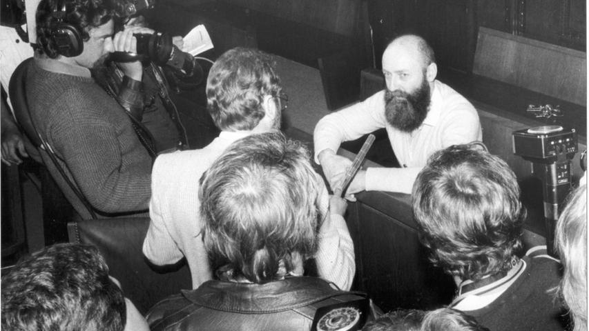 ... Karl-Heinz Hoffmann (hier bei einem Prozess in Nürnberg mit Journalisten) die Tat gestanden haben. Hoffmann konnte nicht nachgewiesen werden, mit dem Mord in Verbindung zu stehen. 1986 erhielt er wegen anderer Delikte eine Freiheitsstrafe von neuneinhalb Jahren wegen Freiheitsberaubung, Nötigung und illegalen Waffenbesitzes.