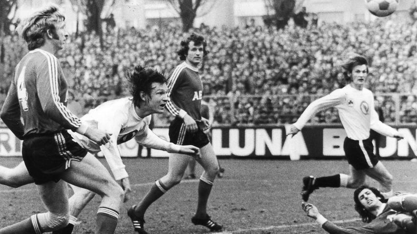 Der 27. Spieltag der 2. Liga Süd in der Saison 1974/75 bedeutete einen Feiertag für den Fürther Schatzmeister. Erstmals in der Vereinsgeschichte nahm man am Ronhof bei einem Spiel mehr als 100.000 Mark ein - exakt waren es 127.000. Sportlich lief es - zumindest, wenn man das Resultat betrachtet - ebenfalls gut für das Kleeblatt, das den Club mit 3:2 (auf unserem Bild köpft Bopp das Tor zum 2:1) in die Schranken wies. Ein wichtiger Erfolg auf dem Weg zum späteren Klassenverbleib. Auf Nürnberger Seite war man hingegen stinksauer...