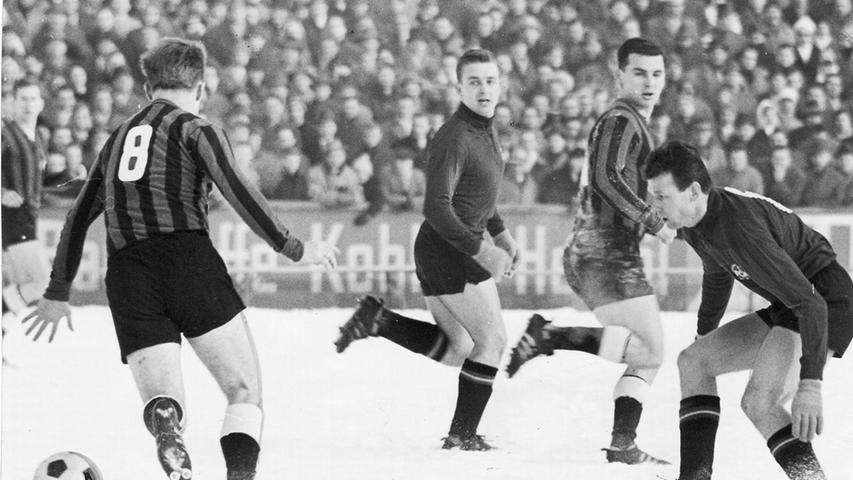 Während der Club die Qualifikation für die Bundesliga schaffte, musste Fürth am Saisonende den Gang in die Regionalliga antreten. Das letzte Oberliga-Derby war damit gleichzeitig auch das letzte Pflichtduell beider Klubs für einige Jahre. Erst nach dem Abstieg des FCN 1969 traf man sich wieder. Auf unserem Bild belauert Clubläufer Gettinger Fürths Halbrechten Schmidt. Flachenecker und Schneider in der Mitte sehen interessiert zu.