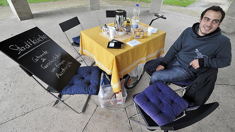 """Experimentierfreudig: Martin Leibinger wartet auf Mitmenschen mit Geschichten, Barbara Engelhard irritiert mit ihrer """"Wartebank"""" Passanten vor dem Hauptbahnhof."""