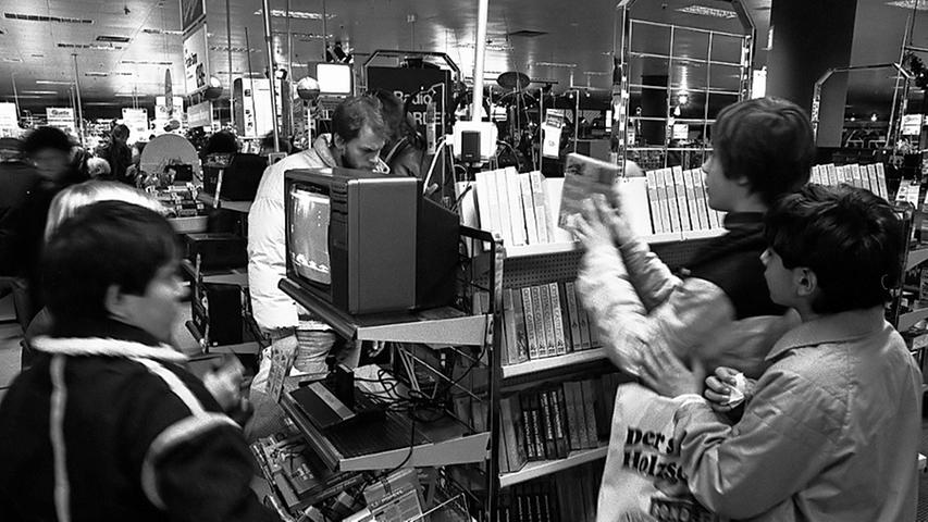 Einkaufstrubel im Dezember '86: Der Nachwuchs steht bei der  Unterhaltungselektronik Schlange. Derweil sorgt im City-Center ein weiblicher Weihnachtsmann für lange Gesichter.