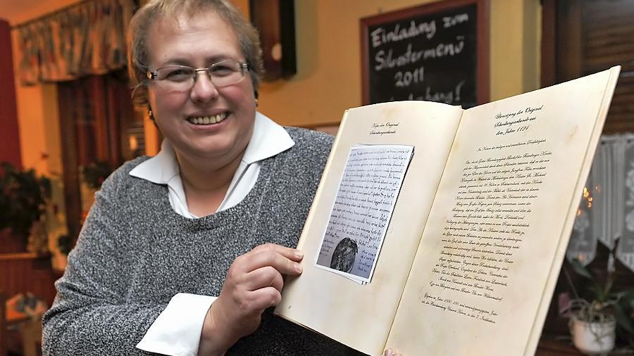 Irmi Schmidt hält den Beweis in Händen — eine Urkunde belegt, dass ihr Heimatdorf vor 888 Jahren zum ersten Mal erwähnt wurde.