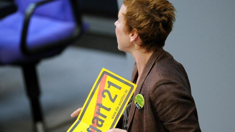 Die Abgeordnete der Linken, Sabine Leidig, hält ein Schild mit einem durchgestrichenen Stuttgart 21-Schriftzug. Sie wurde daraufhin des Plenarsaals verwiesen.