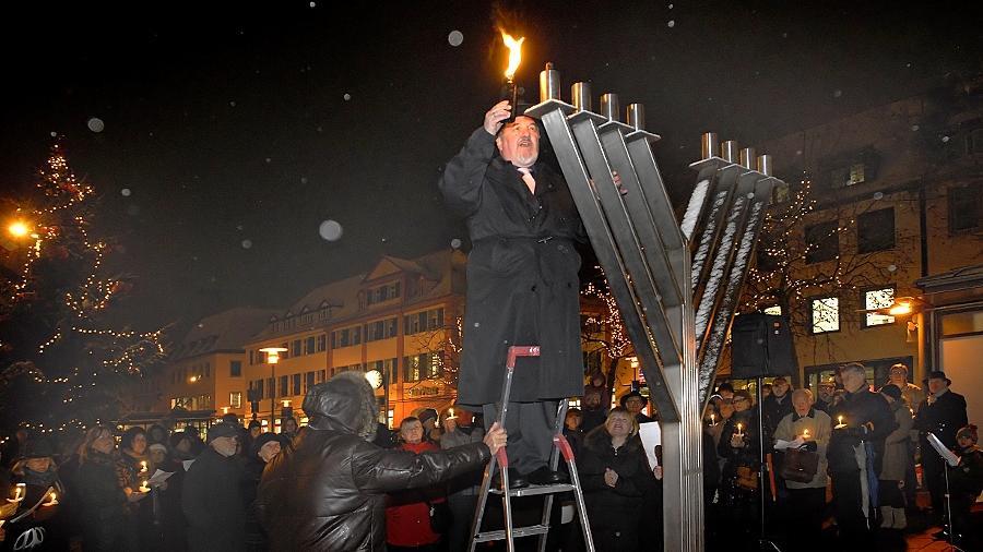 Rabbi Daniel Danieli entzündet die erste Flamme für das Chanukka-Fest auf dem Hugenottenplatz. Auch in Erlangen erleben Mitglieder der Jüdischen Kultusgemeinde, dass sie wegen ihres Glaubens angefeindet werden.