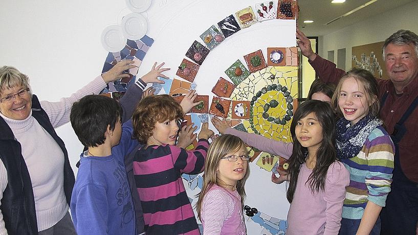 Mit Feuereifer und viel Kreativität verschönern die Schüler der Grundschule Hilpoltstein die Wand der neuen Mensa. Künstler Heinz Krautwurst und seine Frau Renate (l.) leiten die Mädchen und Buben an und unterstützen sie mit Rat und Tat bei der Gestaltung.