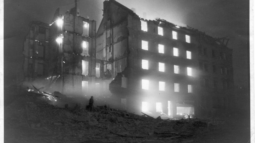 Die Äußere Ziegelgasse nach einem Luftangriff. Aus den nackten Fensterlöchern leuchtet das grelle Licht der Flammen, Hilfskräfte versuchen den Brand mit Wasserschläuchen einzudämmen.