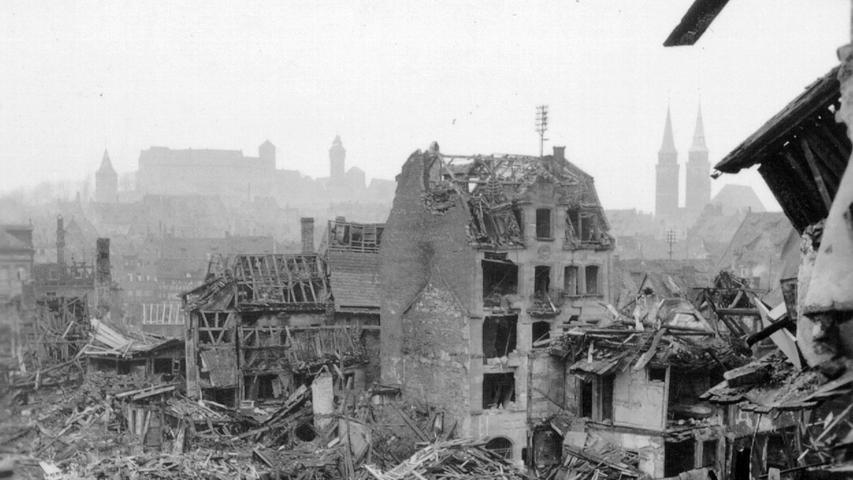 Hinter Trümmerbergen sieht man die Kaiserburg. In den freigeräumten Gassen schauen sich Menschen suchend um.