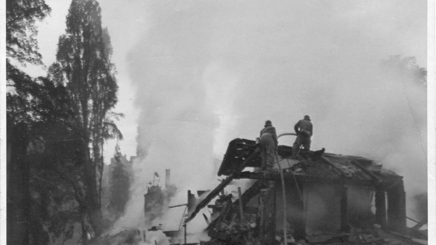 Zwei Feuerwehrler löschen nach einem Bombenangriff die rauchenden Trümmer auf dem Trödelmarkt. (undatiertes Foto)