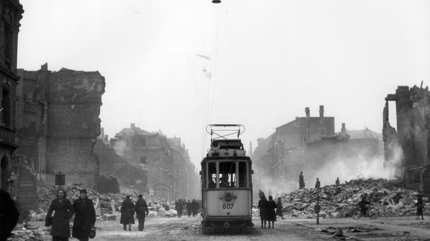 Die Wölckernstraße nach dem Angriff vom 2. Januar 1945, das Wrack einer Straßenbahn steht zwischen den rauchenden Ruinen.