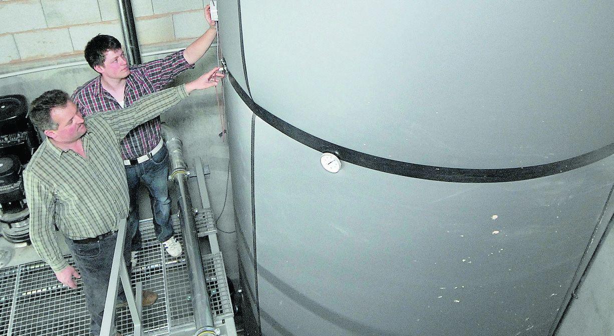 Jürgen Heinl (links) und der 23-jährige Sohn Stefan haben das Projekt mit Mut und Zuversicht angepackt. Neben der Biogasanlage ist der 30000-Liter-Speicher ein zentrales Element des Nahwärmenetzes.