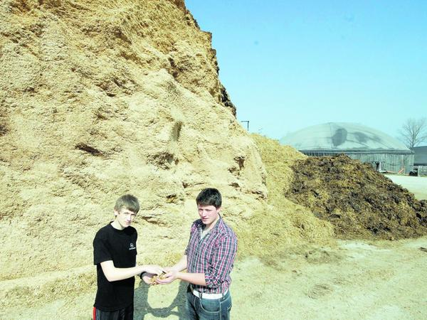 Die Söhne Bernd und Stefan Heinl vor dem Rohstofflager für die Biogasanlage, die hinten zu erkennen ist.