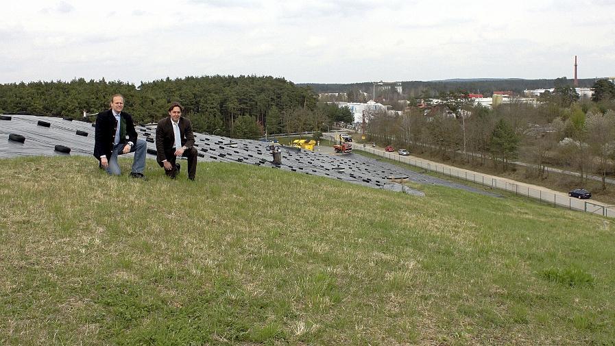 Der bereits abgedeckte Teil der Mülldeponie, auf dem Dr. Gerhard Brunner (li.) und Bürgermeister Ben Schwarz knien, wird zur größten Bürgersolaranlage der Region gemacht. Der hintere, nur mit einer Folie zugedeckte Teil des alten Müllbergs, muss noch warten.