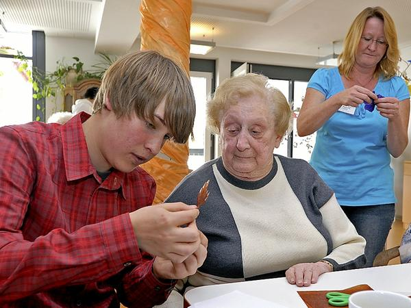 Jens Meiselbach bastelt am Boys' Day mit einer Bewohnerin des Sofienheims.
