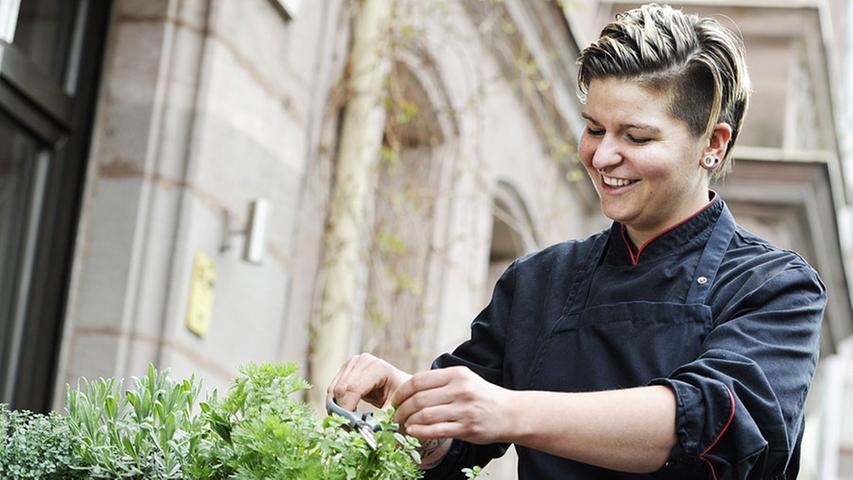 Küchenchefin Diana Burkel schneidet Kräuter.