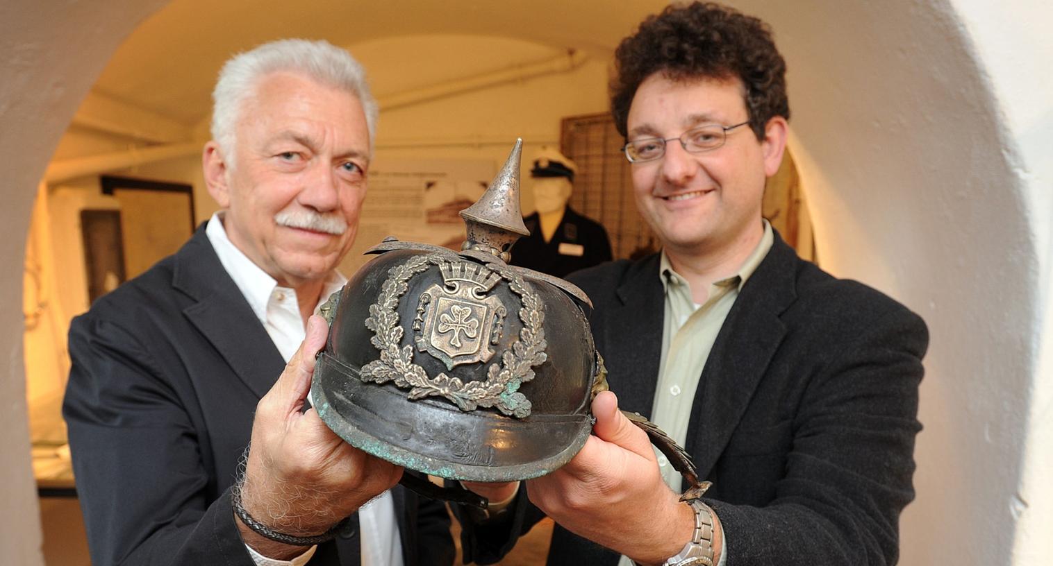 Stadtarchivar Martin Schramm (re.) übergibt Fürths Ex-Polizeichef und Museumsmentor Wilfried Dietsch den schmucken Lederhelm mit Kleeblatt-Wappen.