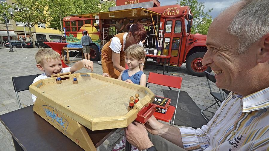 Das Catan-Mobil macht seit gestern Station auf der kleinen Fürther Freiheit: Hier probieren Alexander (7), Bea (5) und die Eltern das Fußballbrettspiel Weykick aus.