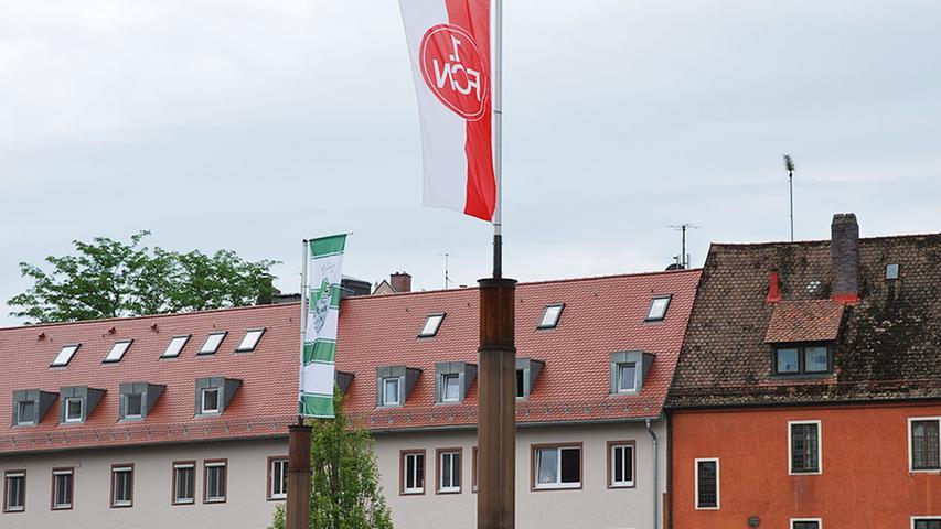 Bisher kann man auf dem Augustinerhof-Parkplatz aber auch schon eine andere versöhnliche Geste entdecken: Hier wehen zur Zeit die Farben der beiden großen fränkischen Fußballvereine. Umso beachtlicher ist die Aktion vor dem Hintergrund, dass Gerd Schmelzer, Besitzer des Augustinerhof-Grundstücks, von 1983 bis 1992 Club-Präsident war.
