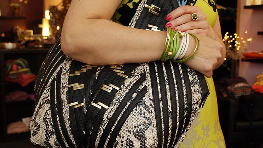 Alles, was frau braucht, passt in den Snakeprint-Shopper von Fiorelli (100 Euro). Der Schmuck (Lederarmbänder von Sence, 50 Euro, Edelstahl-Armbänder von Sence, 3 Euro, Ring mit Strassstein von Sence, 54 Euro) greift die Farben des Kleides gekonnt auf.