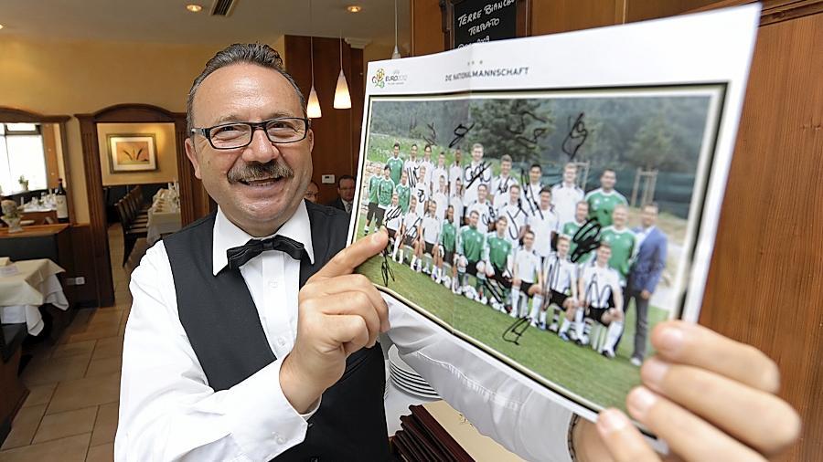 Grüße aus Danzig: La-Palma-Inhaber Gianni Minneci mit der Postkarte der deutschen Nationalmannschaft.
