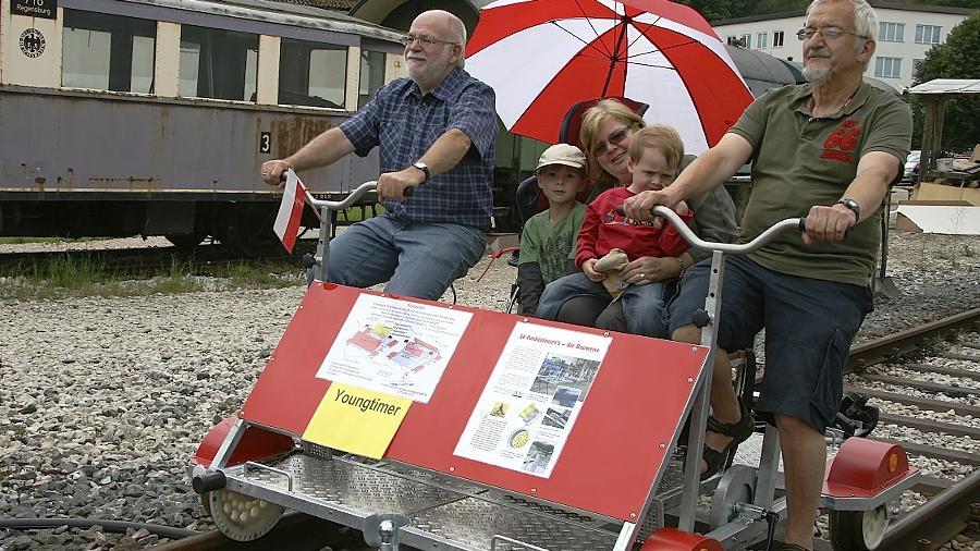 """Mit ihren Enkeln Julian und Tobias ließ sich Christine Johna auf einem Nebengleis auf eine Fahrt mit Karl-Heinz Stammberger (r.)  mit der Fahrrad-Draisine ein. """"Schön, dass wir das mitmachen durften"""", fand die Oma."""