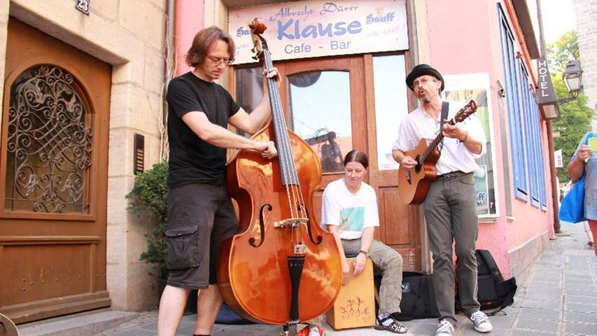 Yellowbelly haben sich am Burgberg platziert. Die eigentlich vierköpfige Band ist mit Kontrabass, Cajon und Gitarre angerückt. Lawrence (rechts) erzählt:
