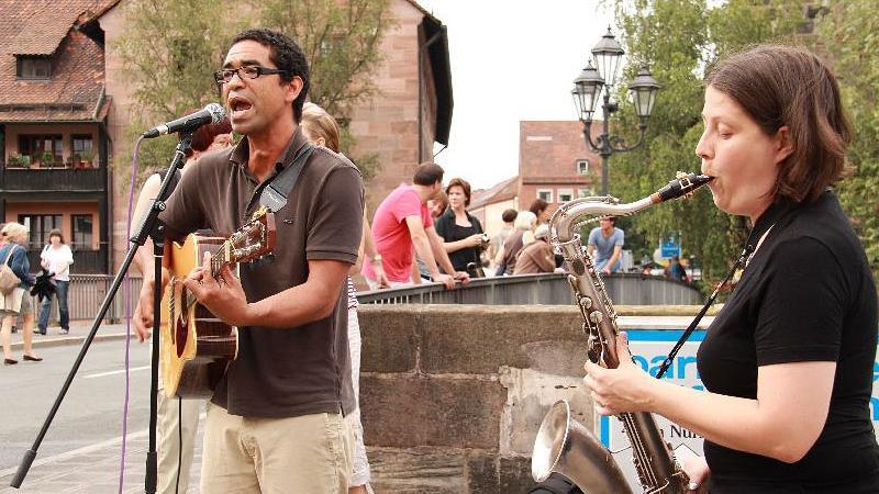 Yapi (links) ist in Nürnberg hinlänglich bekannt. Seine Band Yotho wurde schon  mit dem Kulturpreis ausgeichnet. Er steht zusammen mit Saxophonistin Katja am Pegnitzufer und lässt karibisches Flair aufkommen.