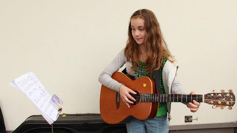 Die zehnjährige Luna Marie wollte schon im vergangenen Jahr beim Bardentreffen ihre Gitarrenkünste zeigen, aber sie fühlte sich noch nicht so weit. Dieses Jahr steht sie auf der Insel Schütt und singt schüchtern deutsche Volkslieder.