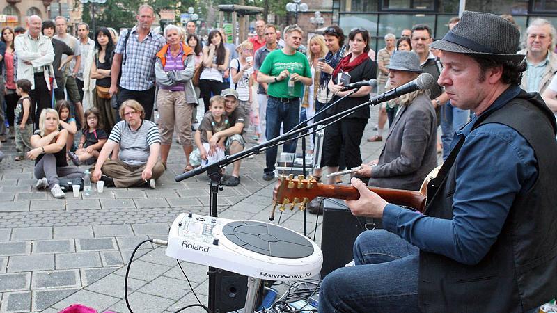Mark Gillespie ist der Gitarrist und Sänger der Mark Gillespie Band aus Gießen an der Lahn. Er hat sich vor der Mauthalle postiert.