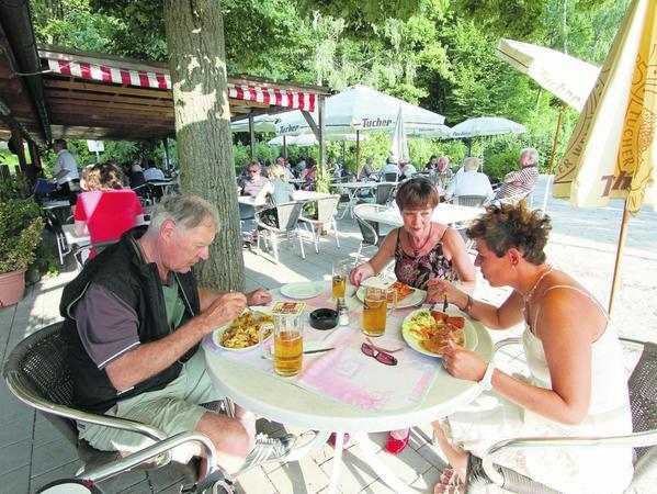 Guten Appetit: Sonnenschirme und eine   Pergola sorgen im Biergarten für Schatten und Regenschutz.