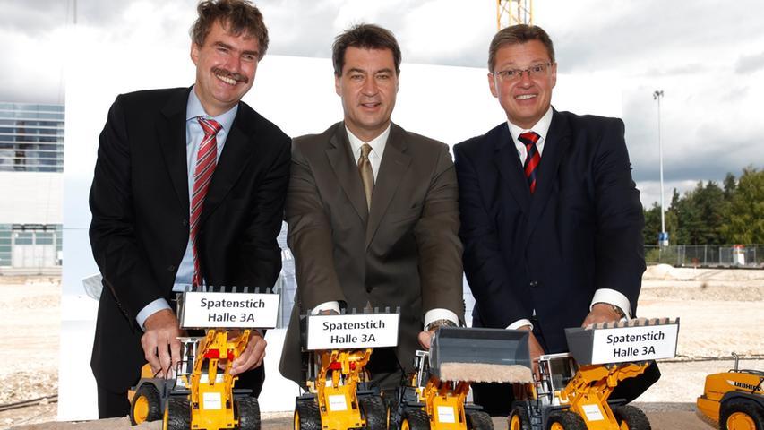 Der erste Spatenstich der neuen Halle 3A im Jahr 2012: Der Geschäftsführer der Messe Nürnberg, Peter Ottmann, der damalige bayerische Finanzminister Markus Söder und Geschäftsführer der Messe Nürnberg Roland Fleck (von links) beim symbolischen Spatenstich mit einem Spielzeugbagger.