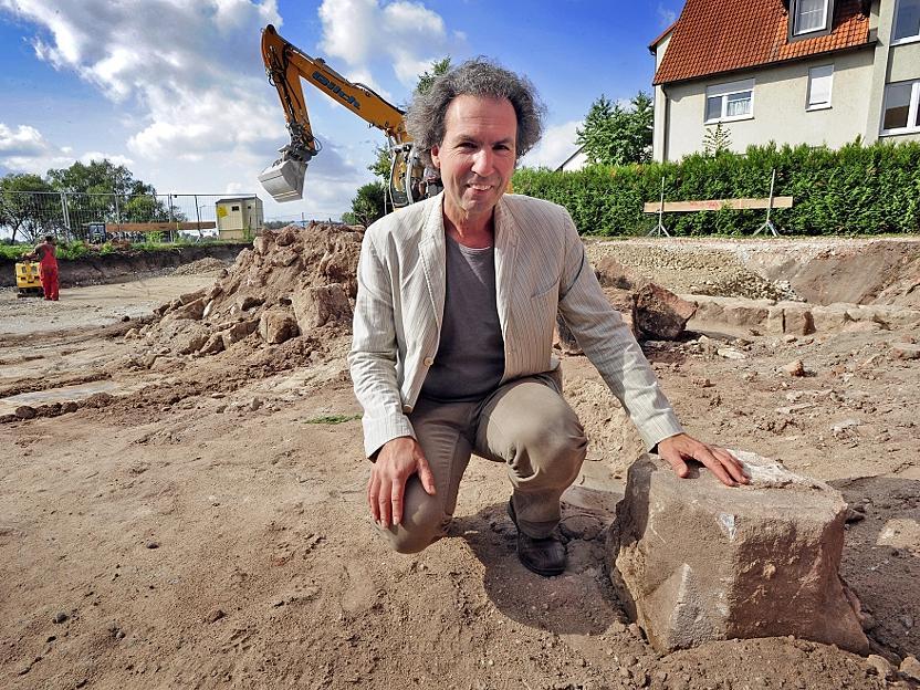 Auf dem Bauglände nimmt Stadtheimatpfleger Alexander Mayer (rechts) den Sockel einer Steinsäule unter die Lupe.