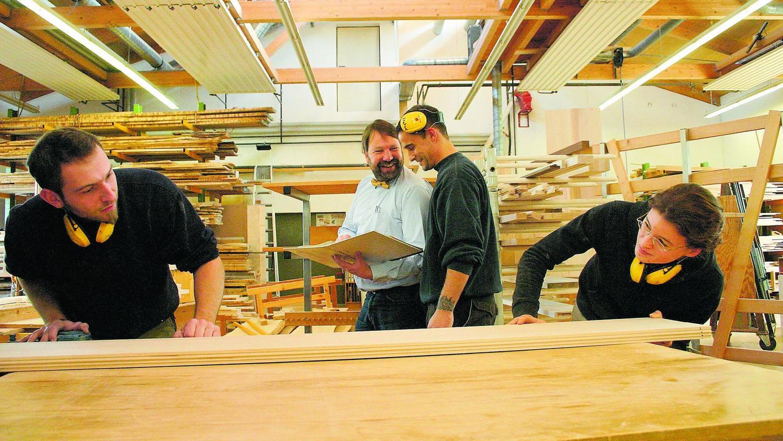 """Herwig Danzer (Mitte) von """"Die Möbelmacher"""" mit Mitarbeitern in der Schreinerei."""