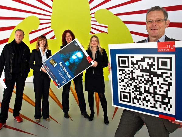 Andreas Radlmaier und Christel Paßmann präsentieren die QR-Codes auf Plakaten