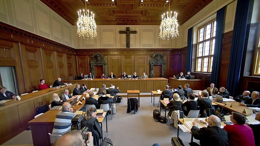 13 Angeklagte, jeweils flankiert von mindestens einem Strafverteidiger, zwei Staatsanwälte (im Bild vorne rechts) und fünf Richter mit einem Ersatzschöffen — allein der personelle Aufwand des Verfahrens ist enorm.