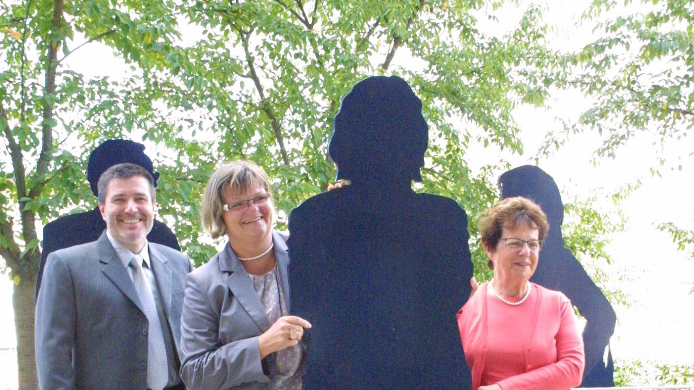"""""""Aus der Mitte"""" heißt das Kunstwerk auf dem Rathausplatz, geschaffen von """"Traktor 26"""" alias Hermann Drescher und Maren Diedrich. Das Paar hat 21 Rednitzhembacher in Stahl verewigt. Gabi Weißmantel versteckt sich ein wenig hinter einer der Stahl-Figuren, doch bei den Führungen wird sie im Vordergrund stehen. Unterstützung erhält sie von Christel Vogelsang (rechts), der Kulturbeauftragten des Gemeinderats, und Bürgermeister Jürgen Spahl."""