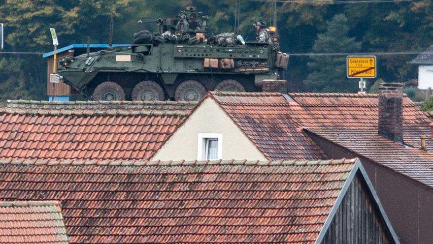 Ein Radpanzer vom Typ Stryker fährt hinter Häusern in Kleinfalz über eine Straße.