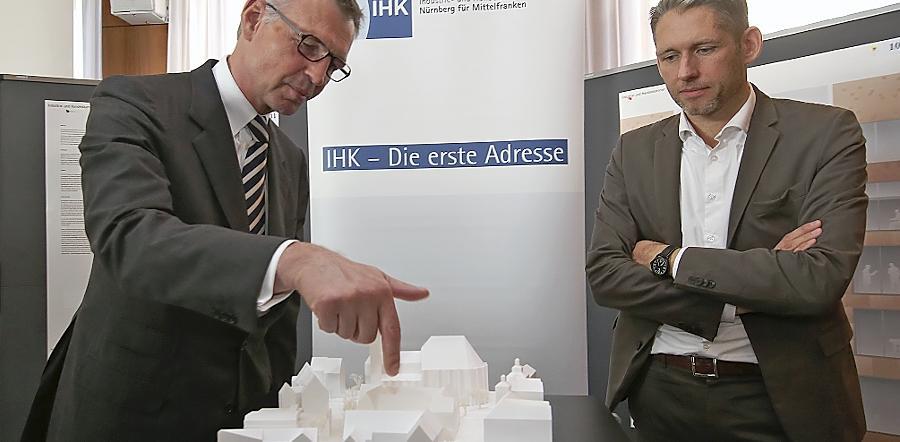 IHK-Präsident Dirk von Vopelius (links) und Architekt Armin Behles begutachten den ausgewählten Enwurf für die Neugestaltung des Nürnberger IHK-Sitzes.