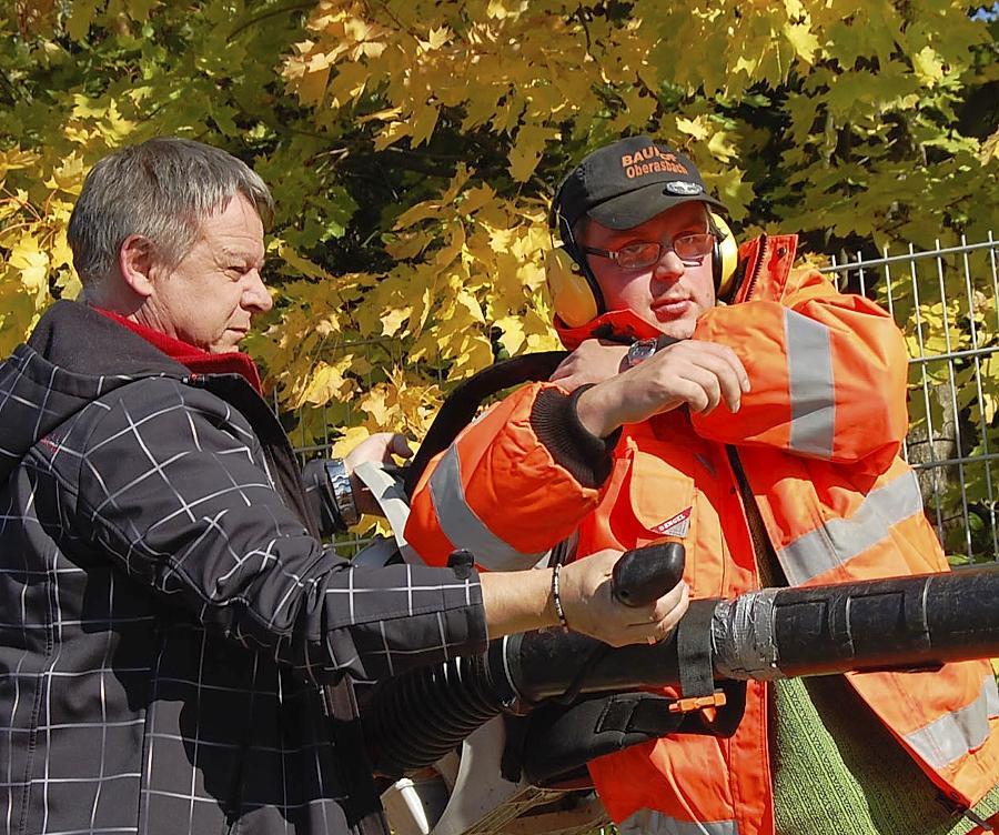 Bauhofleiter Hans-Jürgen Haumer (links) hilft Alexander R., das schwere Laubblasgerät zu schultern.