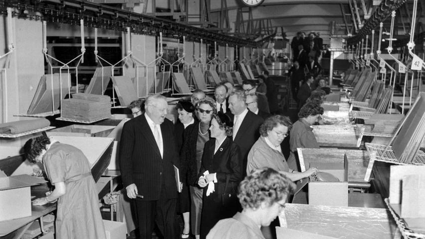 1956 ging auf einem neuen Betriebsgebäude an der Fürther Straße in Nürnberg die automatisierte Versandanlage in Betrieb. Nein, Bundeswirtschaftsminister Ludwig Erhard (links) musste nicht selbst mit anpacken. Aber er machte 1956 einen Rundgang in der neuen Quelle-Packerei. Dabei unterhielt er sich mit Grete Schickedanz (rechts).